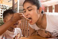 Leuk kind weinig jongen het voeden voedsel aan moeder stock foto's