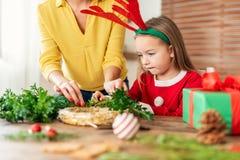 Leuk kleutermeisje rendiergeweitakken dragen en haar moeder die Kerstmiskroon in woonkamer maken De tijdpret van de Kerstmisfamil stock afbeeldingen
