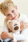 Leuk koestert weinig jongen zijn teddybeer Royalty-vrije Stock Afbeeldingen