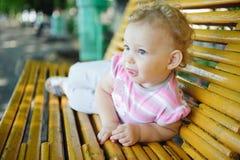 Leuk krullend haired babymeisje op bank Stock Afbeeldingen