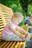 Leuk krullend haired babymeisje op bank Stock Afbeelding