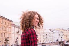 Leuk krullend jong meisje op de achtergrond van de stad Royalty-vrije Stock Afbeeldingen