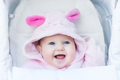 Leuk lachend babymeisje die van een wandelwagenrit genieten Stock Fotografie