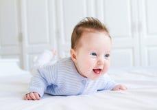 Leuk lachend weinig baby die van haar buiktijd genieten Stock Afbeeldingen