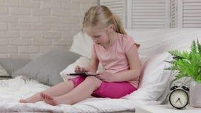 Leuk ligt weinig kindmeisje in de digitale tablet van het bedgebruik stock video