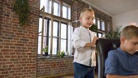 Leuk loopt weinig jongen aan zijn oudere broer die het leren online Engelse lessen op een computertablet terwijl het zitten in stock videobeelden
