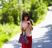 Leuk meisje dat de straat loopt en de telefoon met behulp van royalty-vrije stock afbeeldingen