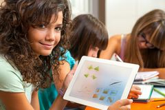 Leuk meisje dat thuiswerk op tablet toont. Royalty-vrije Stock Fotografie