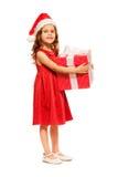 Leuk meisje in de greep reusachtig heden van de Kerstmanhoed Stock Fotografie