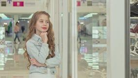 Leuk meisje die aan de camera glimlachen, die de vertoning van de manieropslag onderzoeken stock videobeelden
