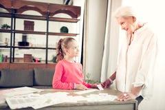 Leuk meisje die aan oma luisteren aandachtig terwijl het bestuderen van brieven royalty-vrije stock foto's