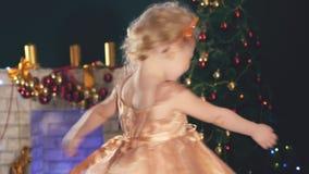 Leuk meisje die, achtergrond verfraaide Kerstboom dansen stock videobeelden