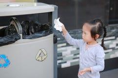 Leuk meisje die afval in de bak zetten openlucht stock afbeeldingen