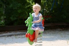 Leuk meisje die bij speelplaats slingeren Stock Fotografie