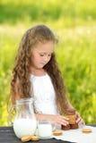 Leuk meisje die chocoladeschilferkoekje op groene achtergrond eten stock foto