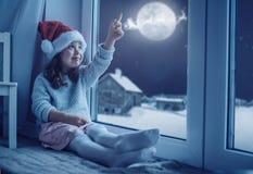 Leuk meisje die de maan bekijken de de winterhemel stock afbeeldingen
