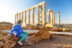 Leuk meisje die de Oude Griekse tempel van Poseidon onderzoeken bij Kaap Sounion, één van de belangrijkste monumenten van de Goud royalty-vrije stock afbeelding
