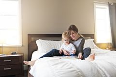 Leuk meisje die een boek met haar moeder in de slaapkamer lezen royalty-vrije stock foto's