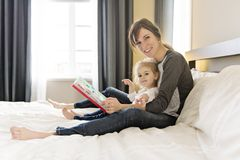 Leuk meisje die een boek met haar moeder in de slaapkamer lezen stock afbeeldingen