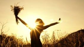 Leuk meisje die een boeket van wildflowers in openlucht golven tegen de heldere zon bij de dag van de zonsondergangzomer Silhouet stock footage