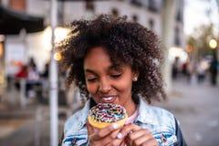 Leuk Meisje die een Donuts eten stock afbeeldingen