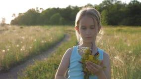 Leuk meisje die in een weide in de kleuren van bloemen in werking stellen Onbezorgde kinderjaren - weinig spel van het kindmeisje stock video