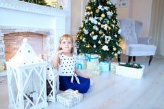 Leuk meisje die en bij camera in studi van het witte Nieuwjaar stellen glimlachen Stock Afbeeldingen