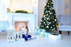 Leuk meisje die en bij camera in studi van het witte Nieuwjaar stellen glimlachen Stock Foto's
