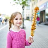 Leuk meisje die gebraden aardappel op een stok eten Royalty-vrije Stock Afbeeldingen