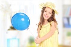 Leuk meisje die in gele kleding een blauwe ballon thuis houden Stock Fotografie