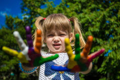 Leuk meisje die haar die handen tonen in heldere kleuren worden geschilderd Lopende Witte Geschilderde Handen Stock Fotografie