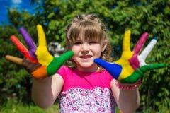 Leuk meisje die haar die handen tonen in heldere kleuren worden geschilderd Lopende Witte Geschilderde Handen Stock Afbeeldingen
