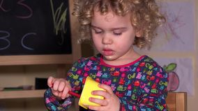 Leuk meisje die haar favoriete yoghurt met lepel eten stock video