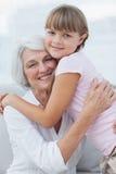 Leuk meisje die haar grootmoeder koesteren stock afbeeldingen