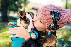 Leuk meisje die haar hond in aard in openlucht kussen royalty-vrije stock foto's