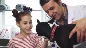 Leuk meisje die haar hond petting tijdens algemeen medisch onderzoek bij de dierenarts clinig stock footage