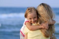 Leuk meisje die haar mamma op het strand koesteren stock foto
