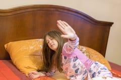 Leuk meisje die haar wapens gelukkig met een glimlach van ontwaken in haar bed uitrekken Kind slaperige geeuw in bed Slaperig wei stock foto