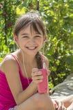 Leuk meisje die in hoofdtelefoons aan de speler luisteren Royalty-vrije Stock Afbeeldingen
