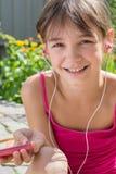 Leuk meisje die in hoofdtelefoons aan muziek luisteren Royalty-vrije Stock Foto's