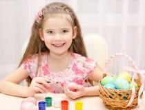 Leuk meisje die kleurrijke paaseieren schilderen Stock Afbeeldingen