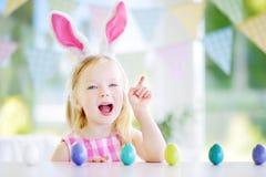 Leuk meisje die konijntjesoren dragen die eijacht op Pasen spelen Stock Fotografie