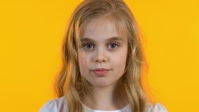 Leuk meisje die met grote ogen camera, kinderjaren, ge?soleerde achtergrond onderzoeken stock footage