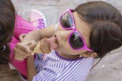 Leuk meisje die met zonnebril een heerlijk roomijs eten stock foto's