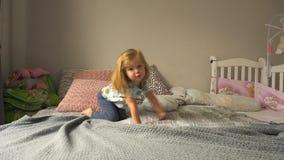 Leuk meisje die op bed kruipen stock video
