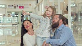 Leuk meisje die op de kledingsopslag op de wandelgalerij richten, die met haar ouders winkelen stock videobeelden