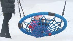 Leuk meisje die op een schommeling op de speelplaats in de winter slingeren stock footage