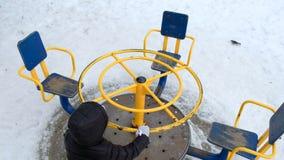 Leuk meisje die op speelplaats bij koude sneeuwdag in de winter slingeren stock videobeelden