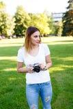 Leuk meisje die op zonnige dag in parkeren met haar camera lopen stock afbeelding
