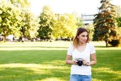 Leuk meisje die op zonnige dag in parkeren met haar camera lopen stock fotografie
